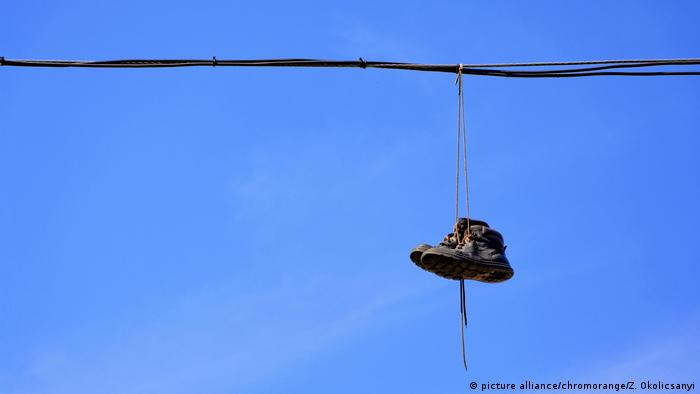 A pair of old boots hanging from an electric cable