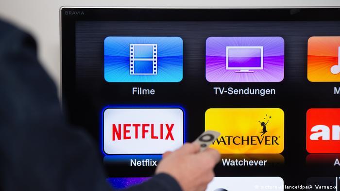 A man clicks on the Netflix logo on a smart TV