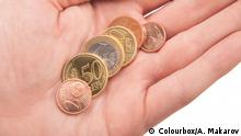 handful of euro coins in hand on white background