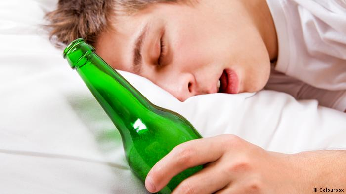 Man sleeps with a beer bottle in bed