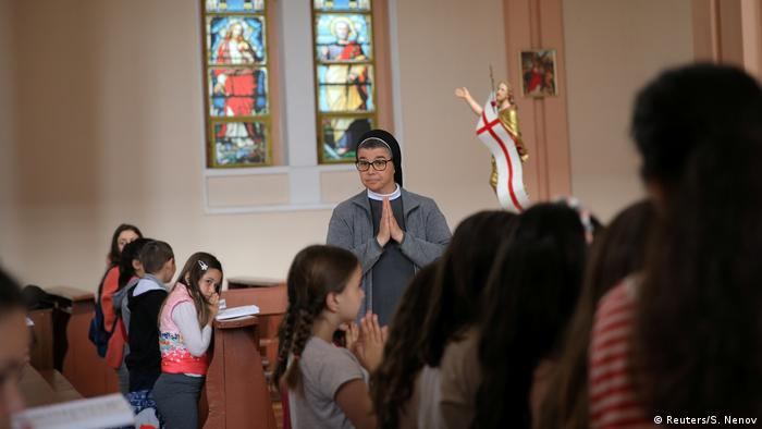 Kids praying with a nun in the Most Holy Heart of Jesus church in Rakovski
