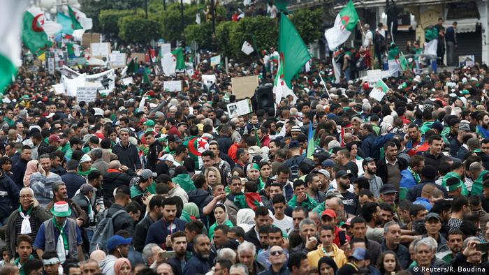 Demonstrators hold flags and banners demanding the departure of Algeria's ruling elite