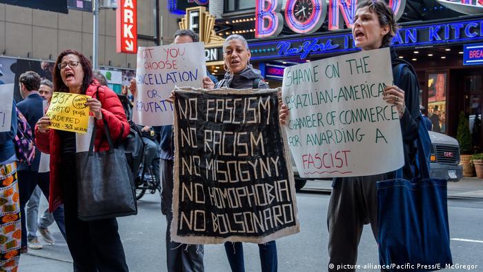 Quatro pessoas seguram cartazes contra Bolsonaro em Nova York
