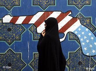 An Iranian woman walk past a mural outside former US embassy
