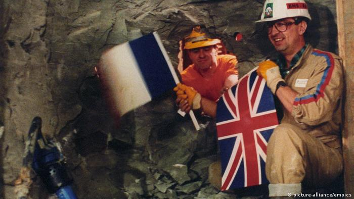 English Channel Tunnel worker Graham Fagg leans through the breakthrough tunnel to exchange flags with French tunnel worker Phillippe Cozette.