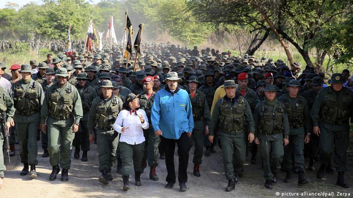 Maduro walks with troops behind him