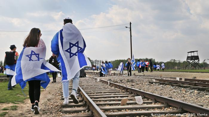 people walking along train tracks wrapped in Israeli flags in Ausschwitz