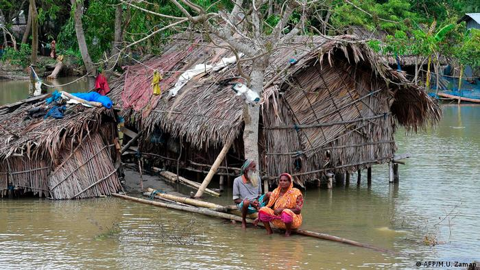 A couple sit outside their flooded home in Bangladesh following Cyclone Fani