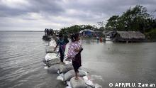 04.05.2019 +++ Bangladeshi children walk over the top of a sandbag embankment that was breached by high waters in Khulna on May 4, 2019, as Cyclone Fani reached Bangladesh. - Cyclone Fani, one of the biggest to hit India in years, barrelled into Bangladesh on May 4 after leaving a trail of deadly destruction in India. (Photo by MUNIR UZ ZAMAN / AFP)