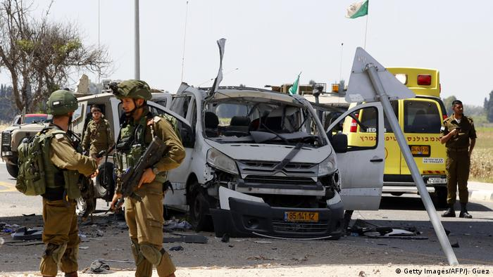 Israeli soldiers gather near a car that was hit by a rocket