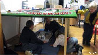 Väter und Kinder spielen unter einem Tisch, auf dem eine Autorennbahn liegt(Foto: Ronny Arnold)