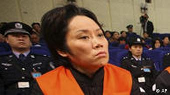 Xie Caiping, left, and other gangster suspects stand trial at the Chongqing No.5 Intermediate People's Court in Chongqing, China, Tuesday, Nov. 3, 2009. The woman called the godmother of a mafia-style gang in China's southern city of Chongqing was sentenced to 18 years in prison Tuesday for running underground casinos and bribing government officials. (AP Photo) ** CHINA OUT **