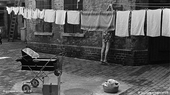 Eine Frau hängt in einem Hinterhof in Leipzig Wäsche auf eine Leine (Foto: transit/Harald Kirschner)