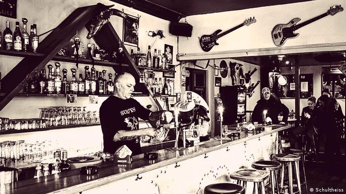 Schwarz-weiß-Foto einer Biertheke, dahinter zapft ein älterer Mann ein Bier (Foto: Schultheiss).