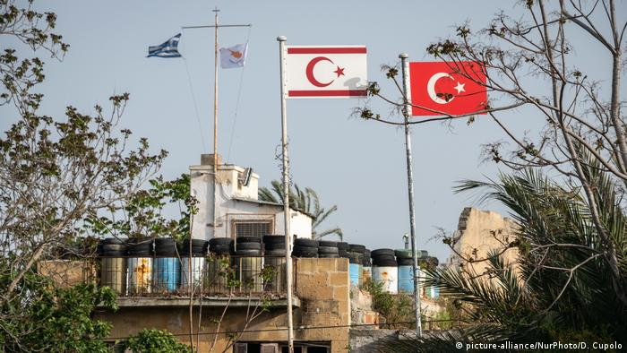 Greek and Cypriot Republic flags are visible across the separating green line from Turkish and Turkish Cypriot flags