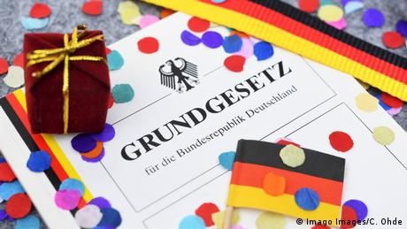 The German constitution, or Grundgesetz, with confetti on top of it (Imago Images/C. Ohde)