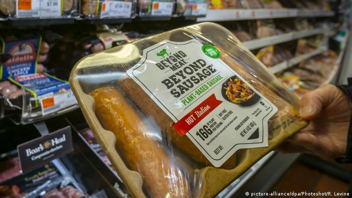 A shopper chooses a package of Beyond Meat brand Beyond Sausage from a cooler in a supermarket in New York