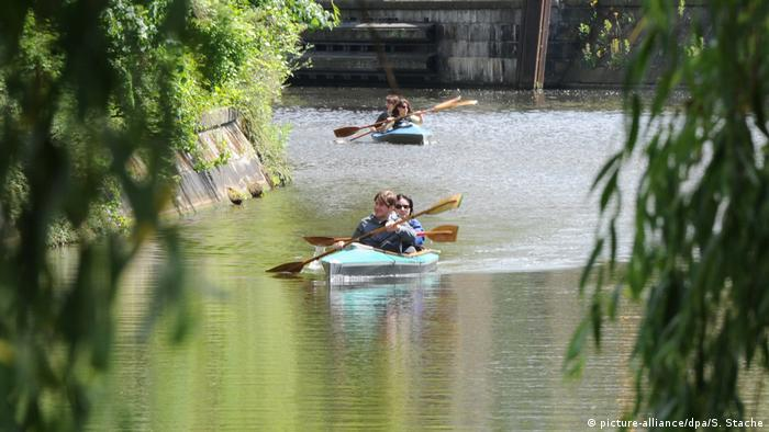 The double kayaks paddel down a canal (Foto: picture-alliance/dpa/S. Stache).