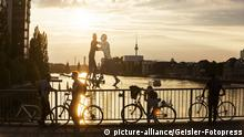 Elsenbrücke over the Spree river at sunset with people on bikes (picture-alliance/Geisler-Fotopress)