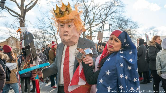 Man wearing Donald Trump head and woman with US flag hijab