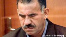 In einigen Unterlagen blättert der angeklagte Chef der verbotenen Arbeiterpartei Kurdistans (PKK), Abdullah Öcalan, als am 31.5.1999 in einem Militärgericht auf der Gefängnis-Insel Imrali (Türkei) der Prozeß gegen ihn eröffnet wird. Öcalan ist am 29.6.1999 zum Tode verurteilt worden. Das Staatssicherheitsgericht verurteilte den Kurdenführer wegen Angriffs auf die Einheit des Staates und wegen tausendfachen Mordes. Öcalan nahm die Urteilsverkündung ohne sichtliche Regung entgegen. Er stand in seinem Glaskäfig und hatte die Arme hinter dem Rücken verschränkt. Der PKK-Chef hatte vor der Urteilsverkündung in seinem «letzten Wort» noch einmal betont, daß er kein Vaterlandsverräter sei. |