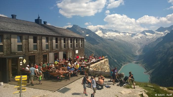 Olpererhütte mountain hut exterior with terrace and Alps and alpine lake in the background, (DAV/C. Reiff)
