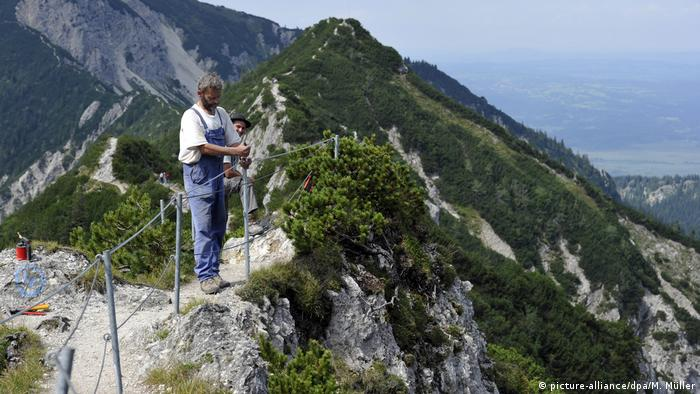 Man repairing security fence on mountain path in Herzogstand, Bavaria (picture-alliance/dpa/M. Müller)