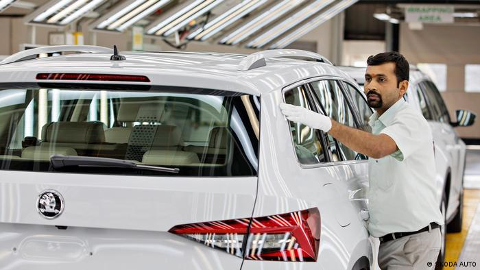 Работник автозавода Škoda в Индии рядом с новыми автомобилями