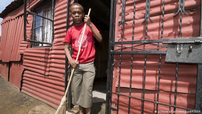 Junge fegt mit dem Besen vor der Blechhütte, Township Soweto, Gauteng, Südafrika, Afrika
