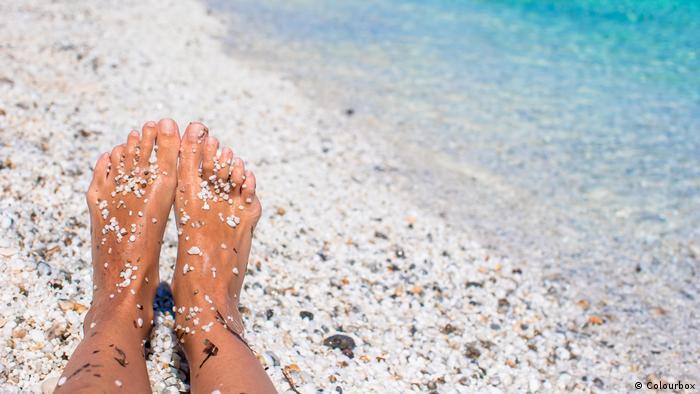 Close-up of female legs on white sandy beach (photo: Colourbox).