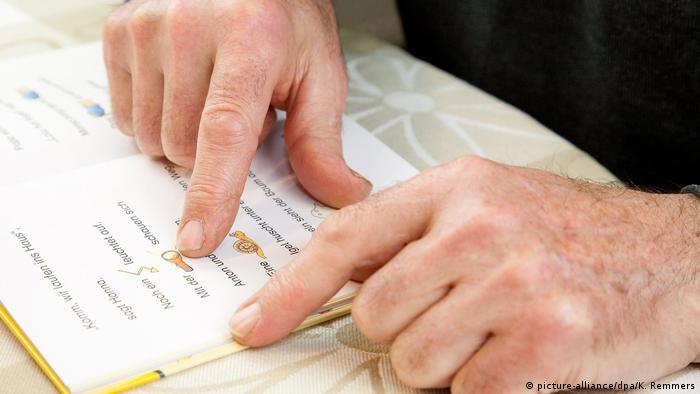 Older man reading through basic reading book