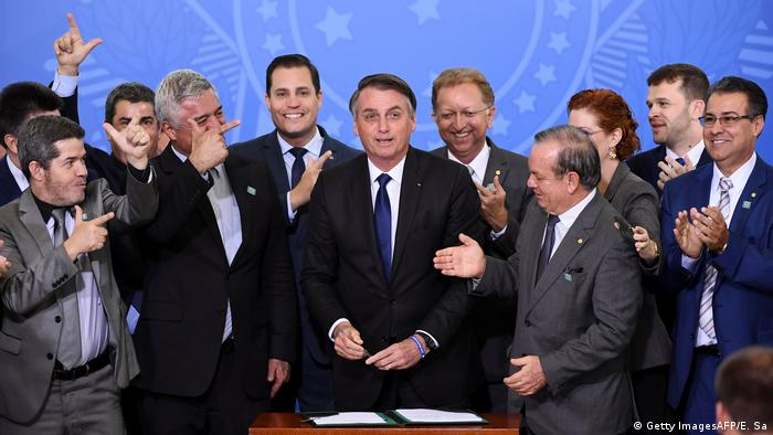 Brazil's president Jair Bolsonaro (center) surrounded by lawmakers while signing the decree to relax gun laws in May 7 (Getty ImagesAFP/E. Sa)