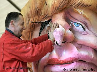 Jacques Tilly repairs a carnival float depicting Chancellor Angela Merkel