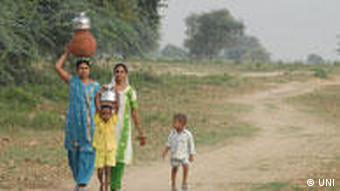 A woman and her children carry pots of drinking water in rural India