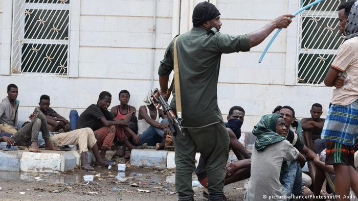 مهاجرون أفارقة في عدن ورجل أمن يراقبهم في مركز احتجاز بمدينة عدن