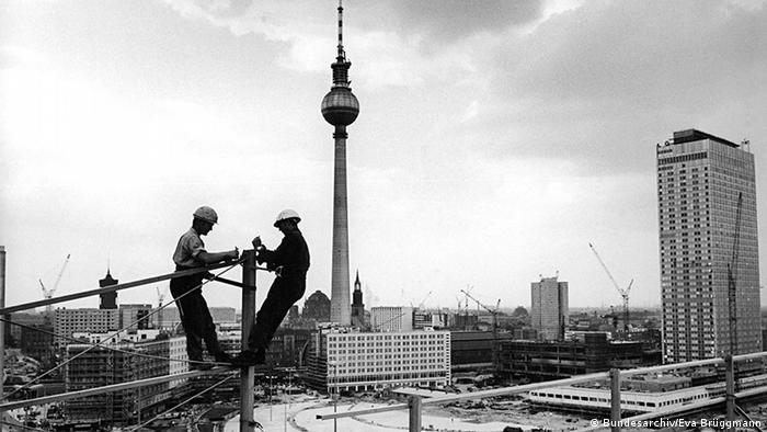 Black-and-white photo of construction workers mounting a neon sign on the Haus der Statistik (Bundesarchiv/Eva Brüggmann)