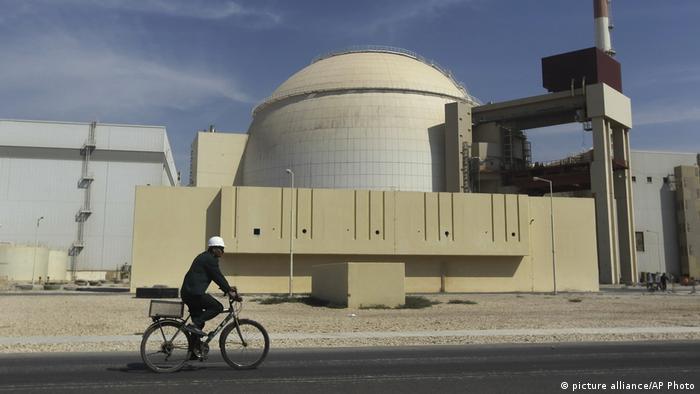 Ein Mann mit weißem Schutzhelm fährt auf einem Fahrrad am Meiler des iranischen Atomkraftwerks in Buschehr vorbei