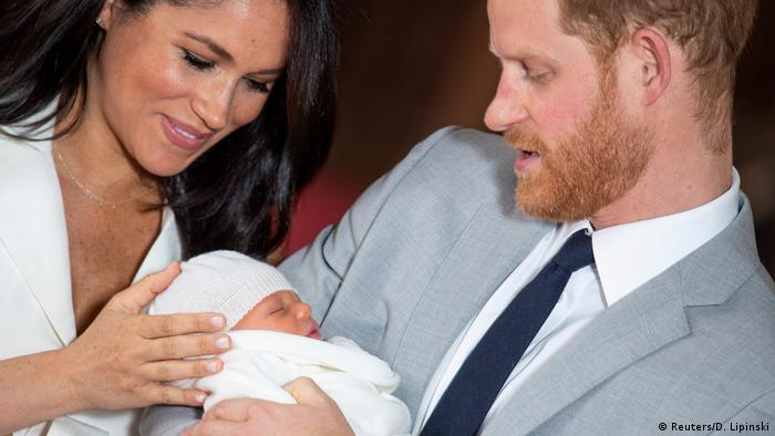 Harry segura Archie no colo. Megan acaricia o bebê.