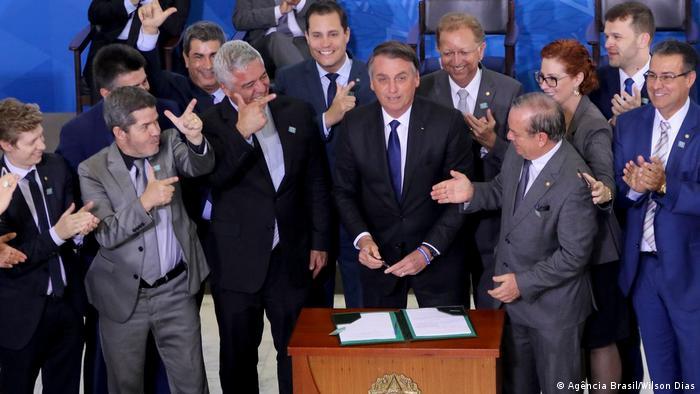 Bolsonaro ao lado de parlamentares durante assinatura de decreto sobre porte de armas em maio de 2019