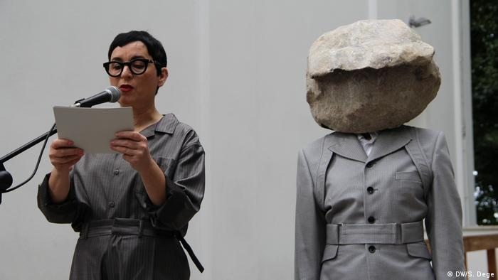 a woman speaking into a mike and another person wearing a head-covering mask