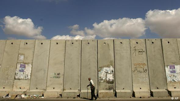 An elderly Palestinian man walks by a section of Israel's separation barrier at the Kalandia checkpoint between the outskirts of Jerusalem and the West Bank town of Ramallah, Saturday, Oct. 6, 2007. (AP Photo/Muhammed Muheisen)