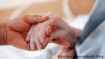 A hand of a younger person holds an older person's hand (picture-alliance/dpa/O. Berg)