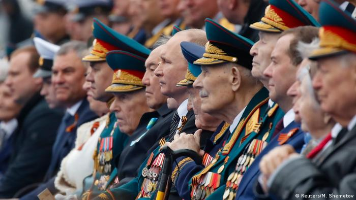 Russian President Vladimir Putin sits along with other Russian generals, officials and guests.