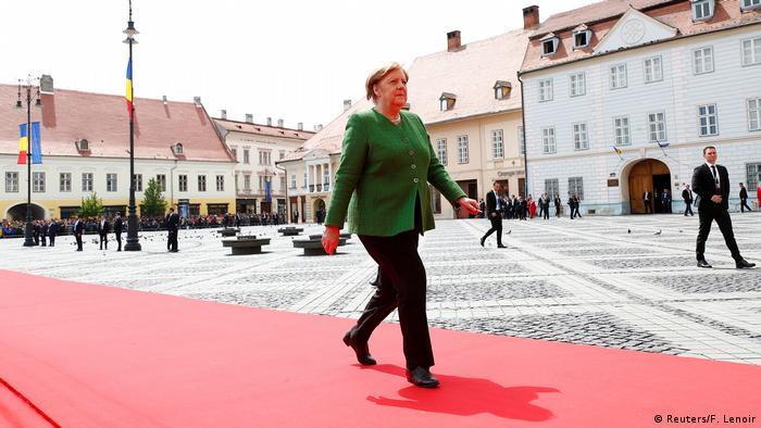 Angela Merkel arriving in Sibiu, walking on a red carpet