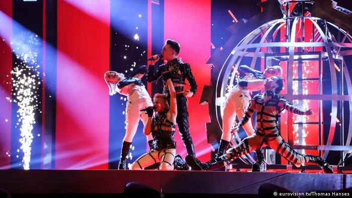 Singer and three dancers in sado-maso garb onstage in front of what looks like a spherical metal cage (eurovision.tv/Thomas Hanses)