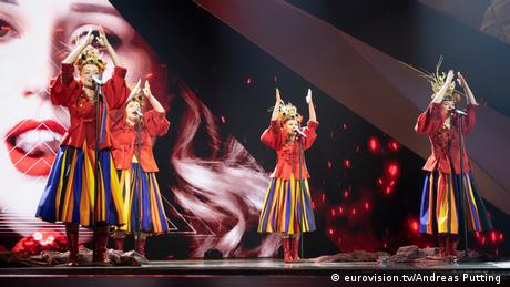 Four women wearing red blouses, colorful skirts and traditional headdresses sing in front of a video projection of a woman, close-up (eurovision.tv/Andreas Putting )