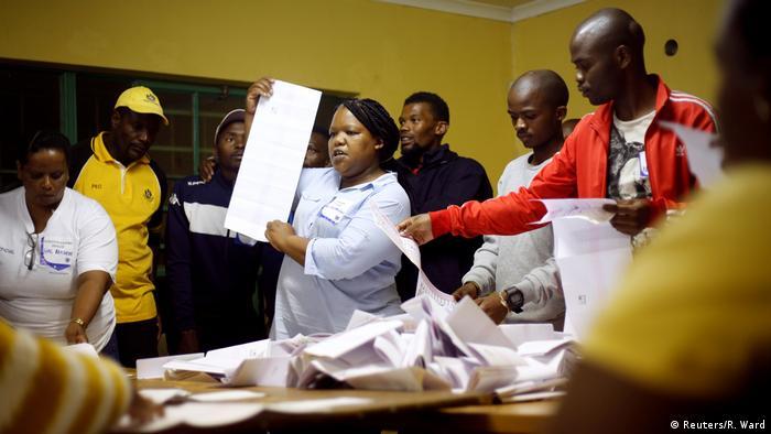 Apuradora de votos mostra folha de papel, cercada por fiscais durante contagem de voto na África do Sul