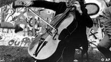 ** FILE ** Famous Russian and American cellist and conductor Mstislav Rostropovich plays in front of the Berlin wall on Nov. 11, 1989. Rostropovich has died, his spokeswoman Natalia Dollezhal said Friday April 27, 2007. Rostropovich had been hospitalized in February for an undisclosed illness and looked frail at his 80th birthday celebration late last month. (AP Photo)