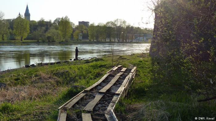 Доски, положенные вдоль берега реки рядом с крепостью