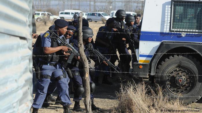 Südafrikanische Polizeibeamte hinter einem Streifenwagen